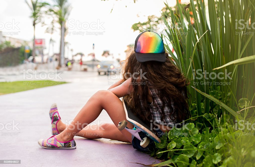 Skateboarder with obscured face sitting on the street. stock photo