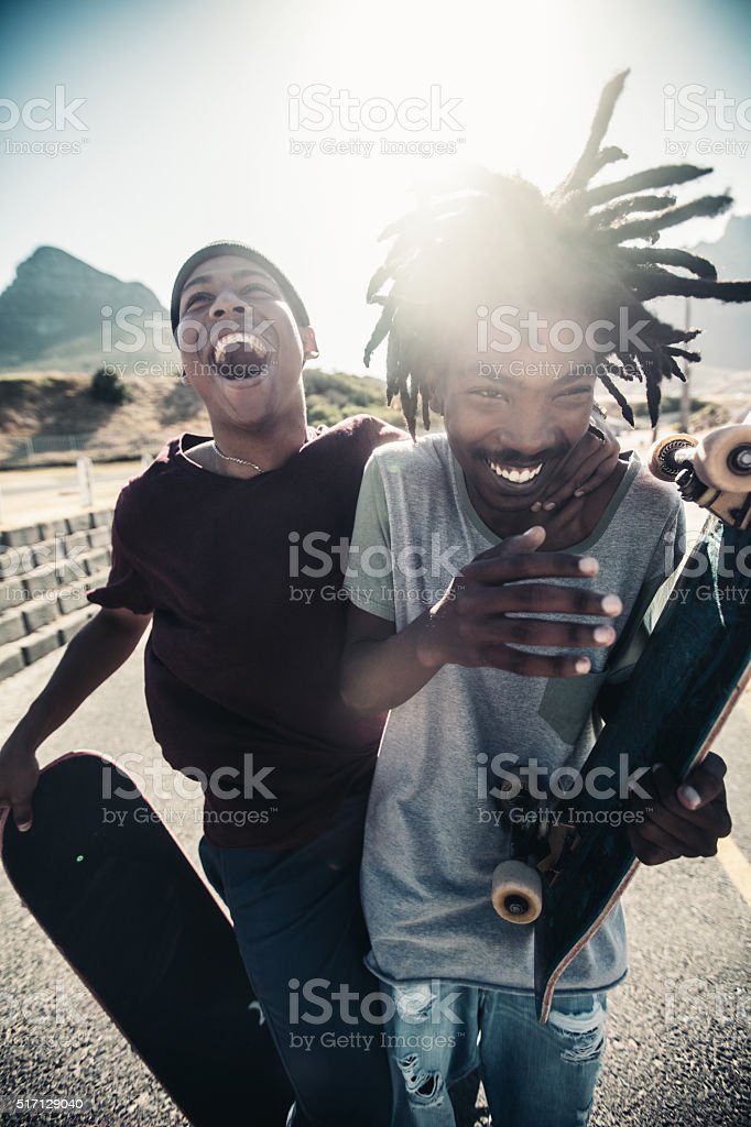 Skateboarders Laugh Together, Outside, With Skateboards in Hand stock photo