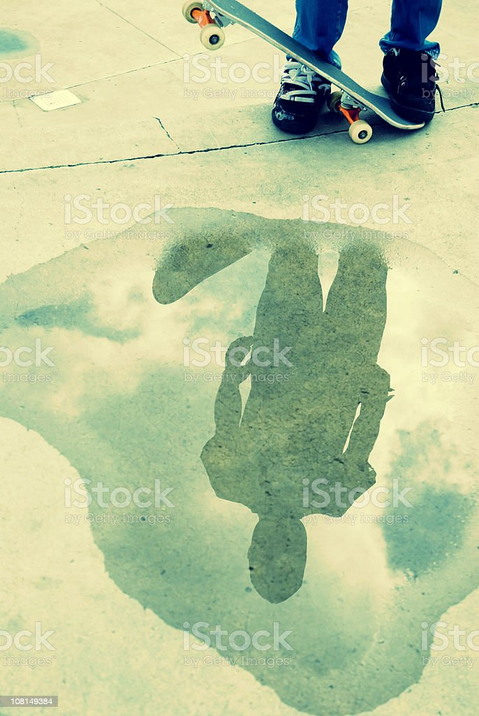 Skateboarder's Reflection in Wet Puddle on Sidewalk royalty-free stock photo