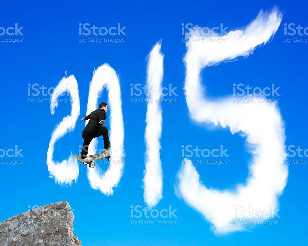 Skateboarding businessman passing through 2015 shape cloud on bl stock photo