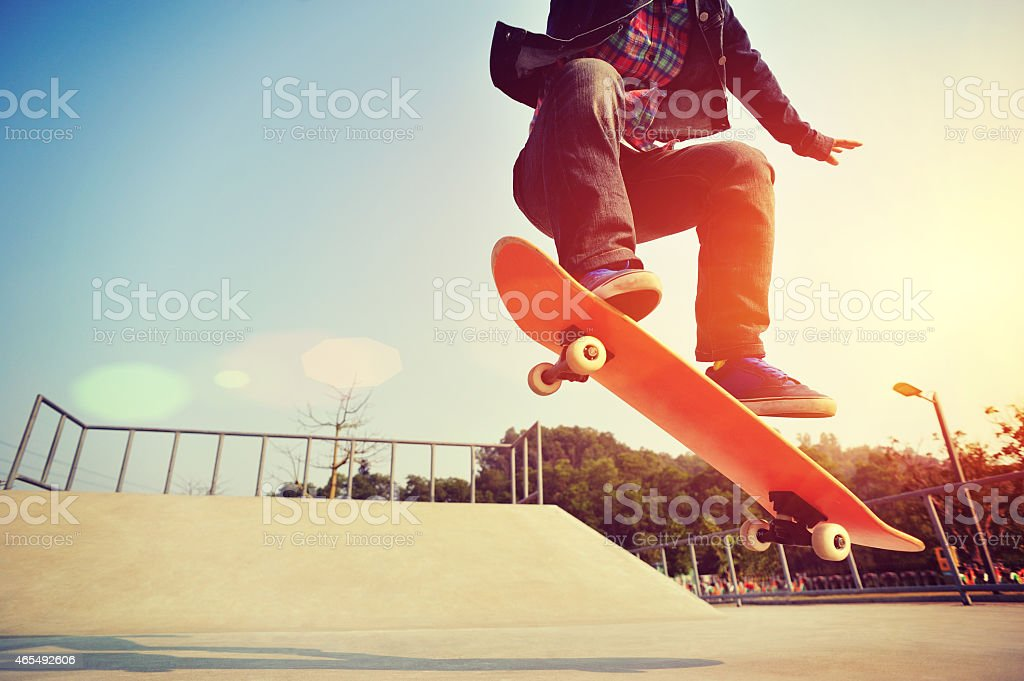 skateboarding  jumping at  sunrise stock photo