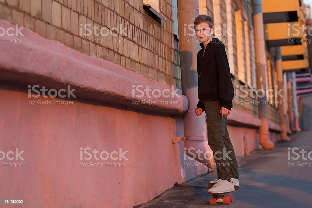 Skateboarding teenager riding right on sunset city street stock photo