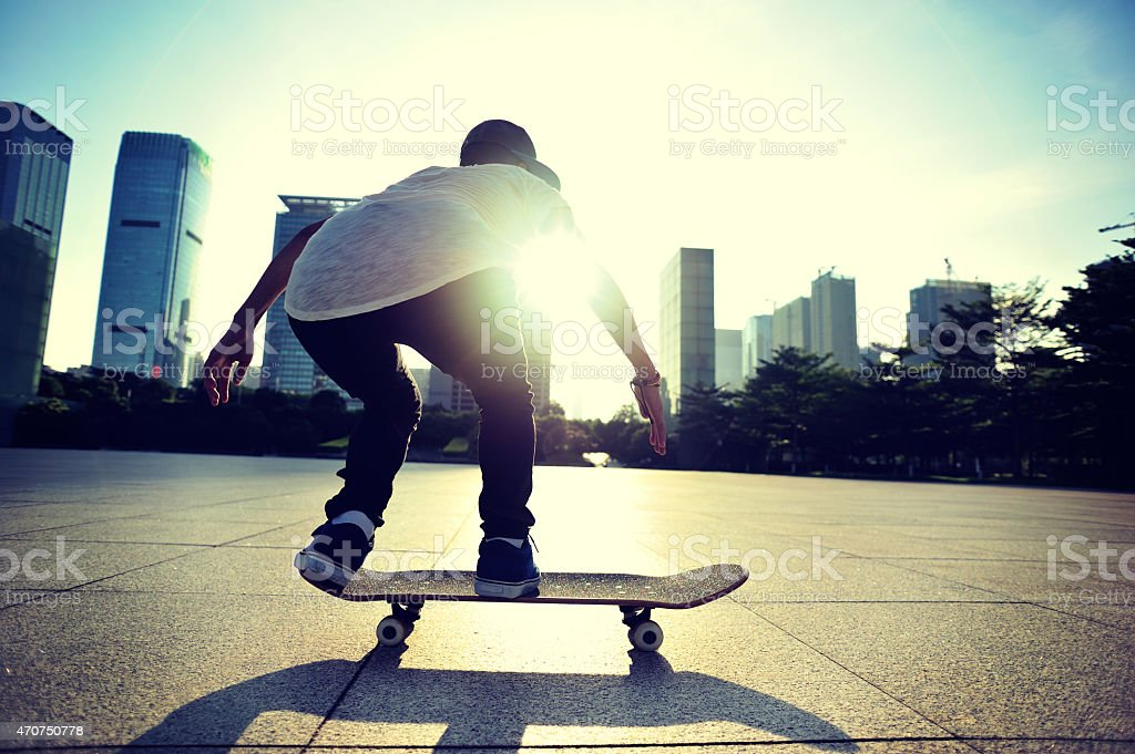 skateboarding woman at city stock photo