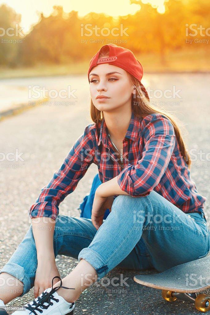 Skateboarding woman at sunset stock photo