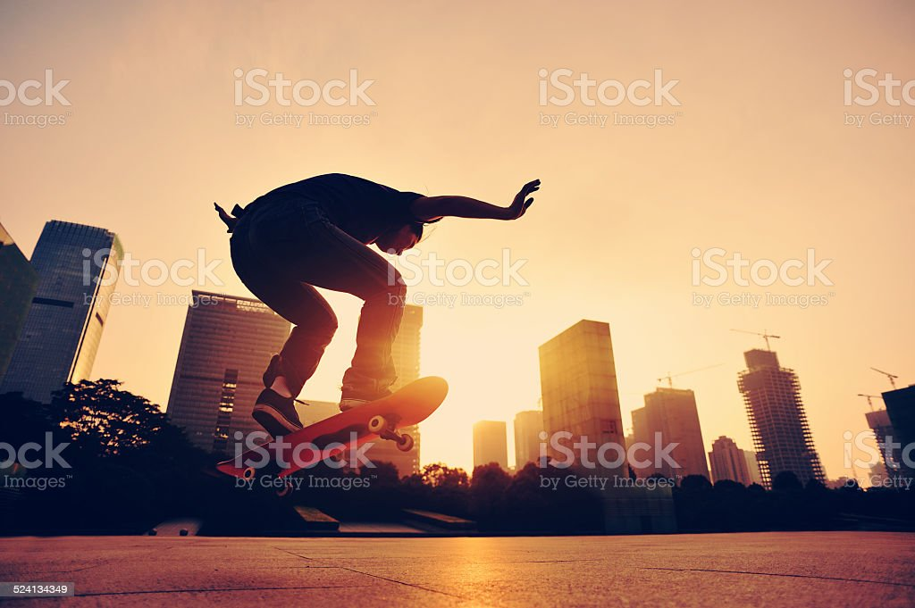 skateboarding woman jumping at  sunrise stock photo