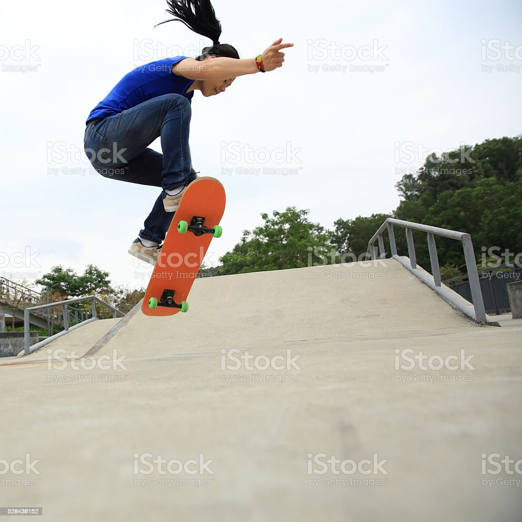 skateboarding woman practice ollie at skatepark stock photo