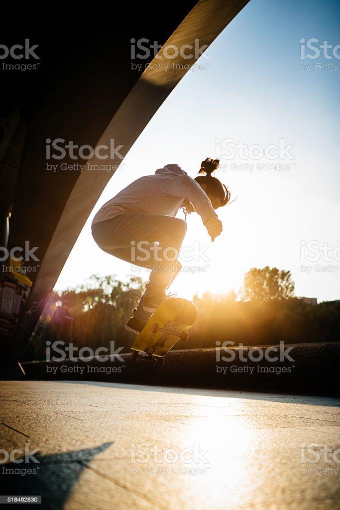 Skater Girl Flipping Skateboard stock photo