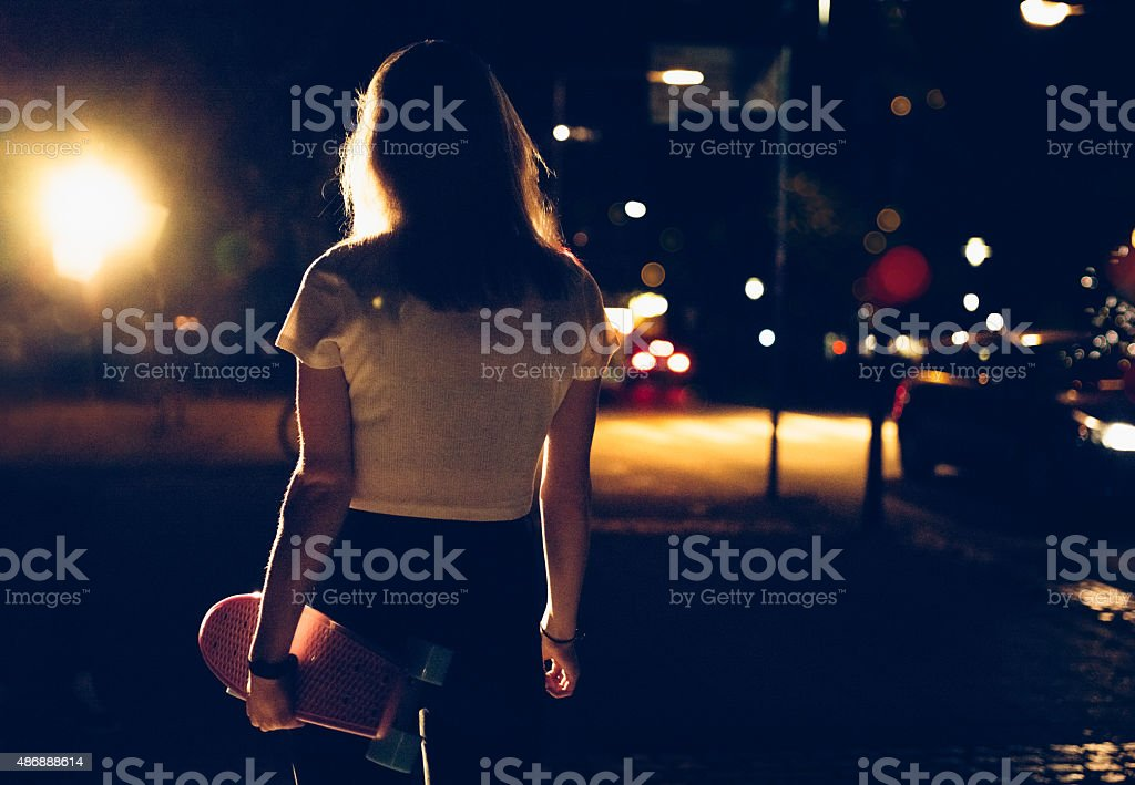 Skater girl walking alone with her skateboard at night stock photo