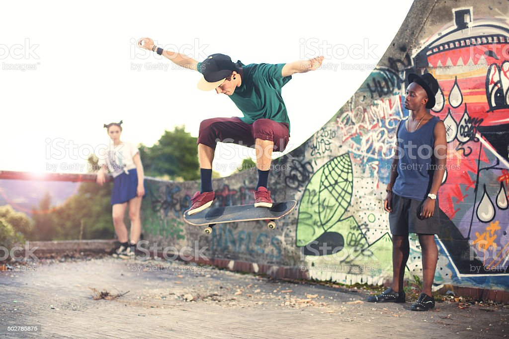 Skater in movement making a trick with friends stock photo