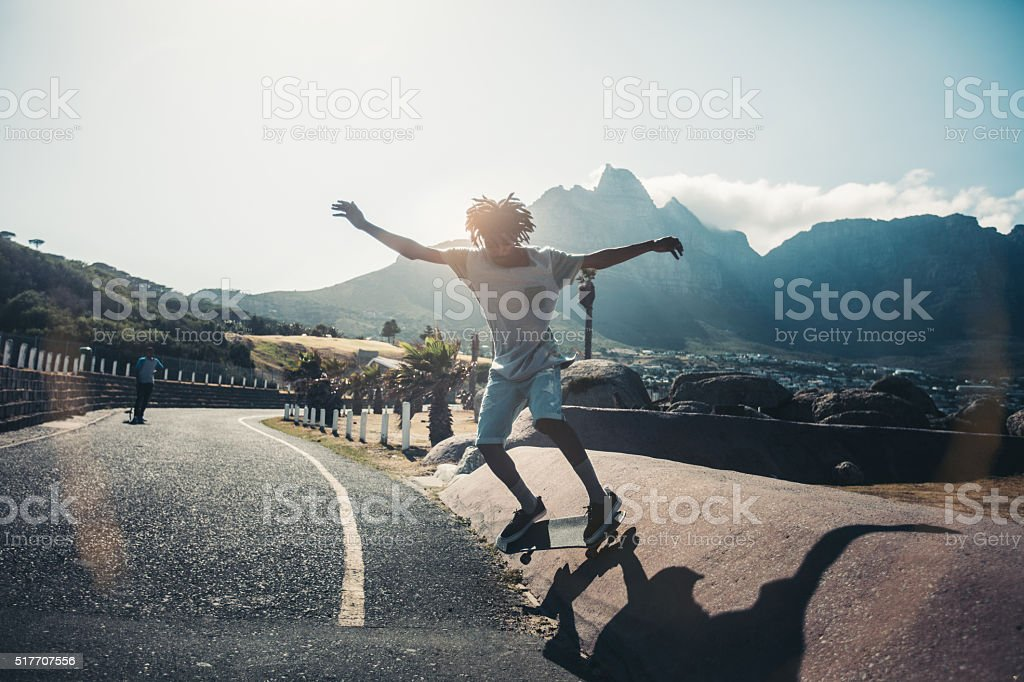 Skater Jumps off Side of Street Curb During Sunset stock photo