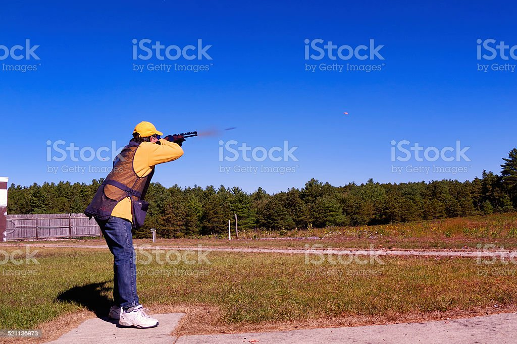 Skeet Shooter with targets in the air stock photo