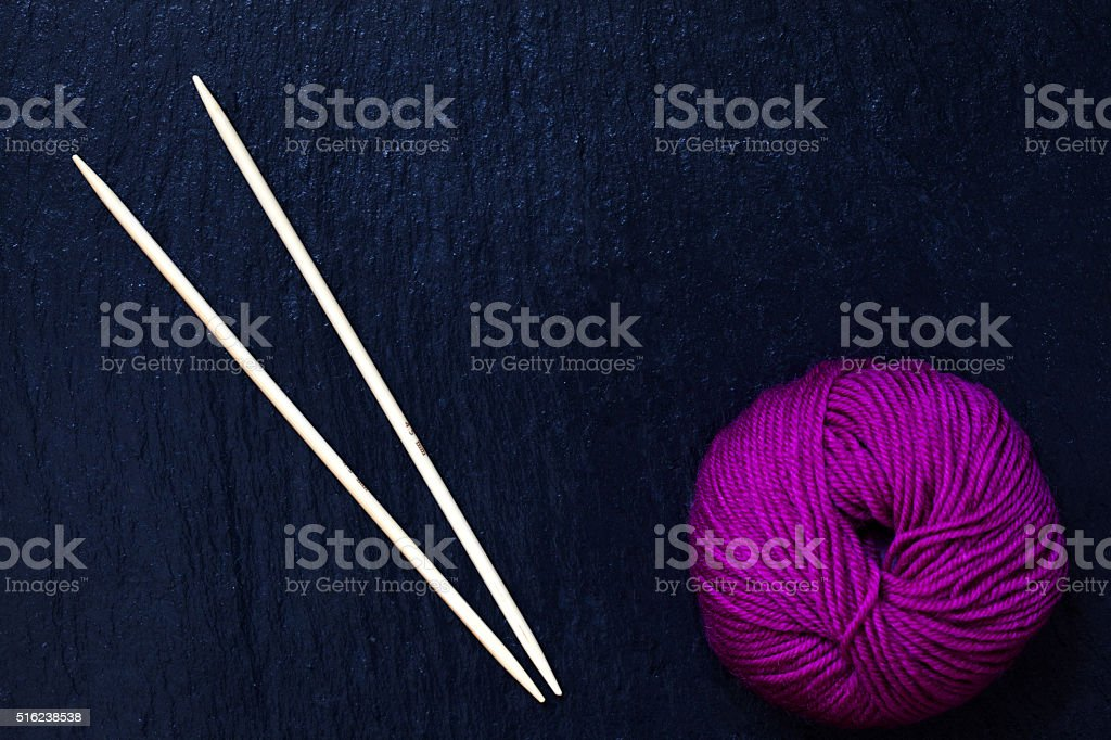 skein of pink yarn with knitting needles with black slate background stock photo