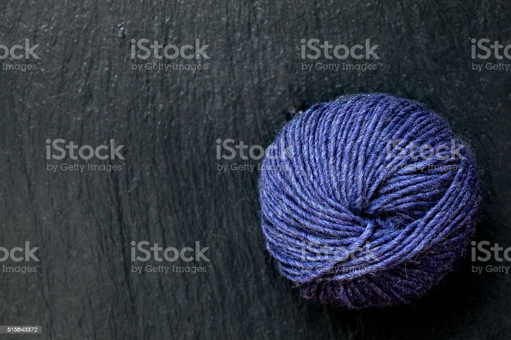 skein of purple yarn with black slate background stock photo