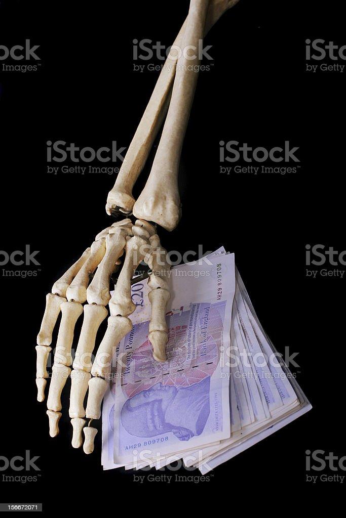 Skeletein hand & money stock photo