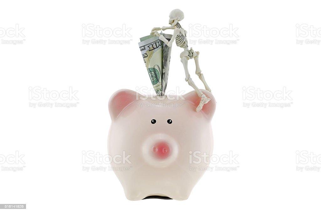 Skeleton climbing on pink piggy bank with American dollar money stock photo