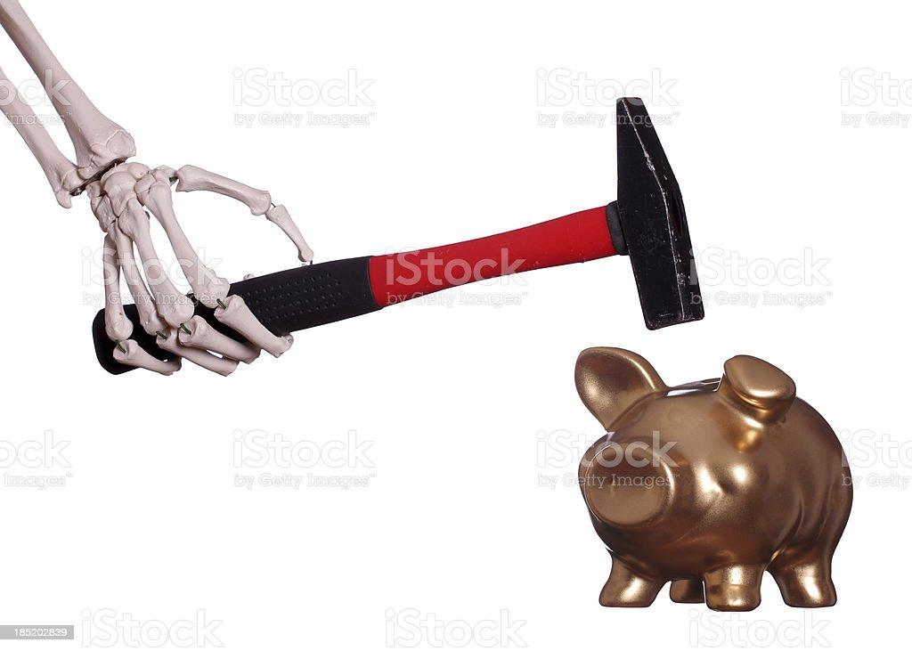 skeleton hand with hammer and golden piggybank stock photo
