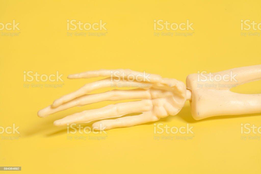 skeleton human hand on yellow background stock photo
