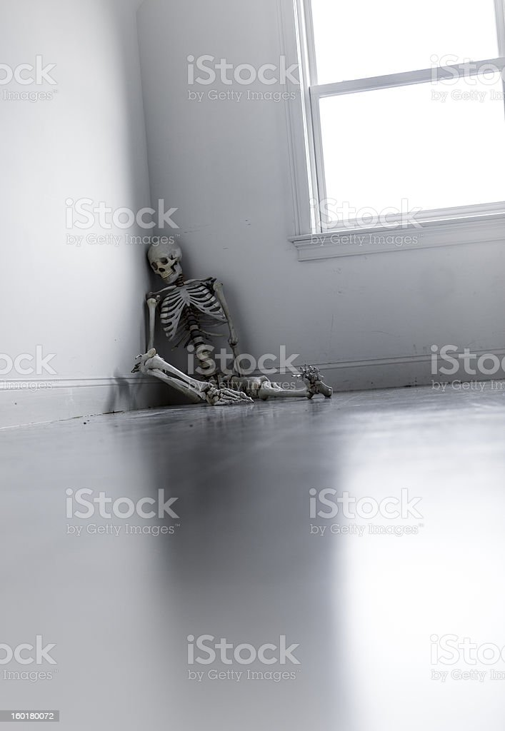 skeleton in a corner of an empty abandoned room royalty-free stock photo