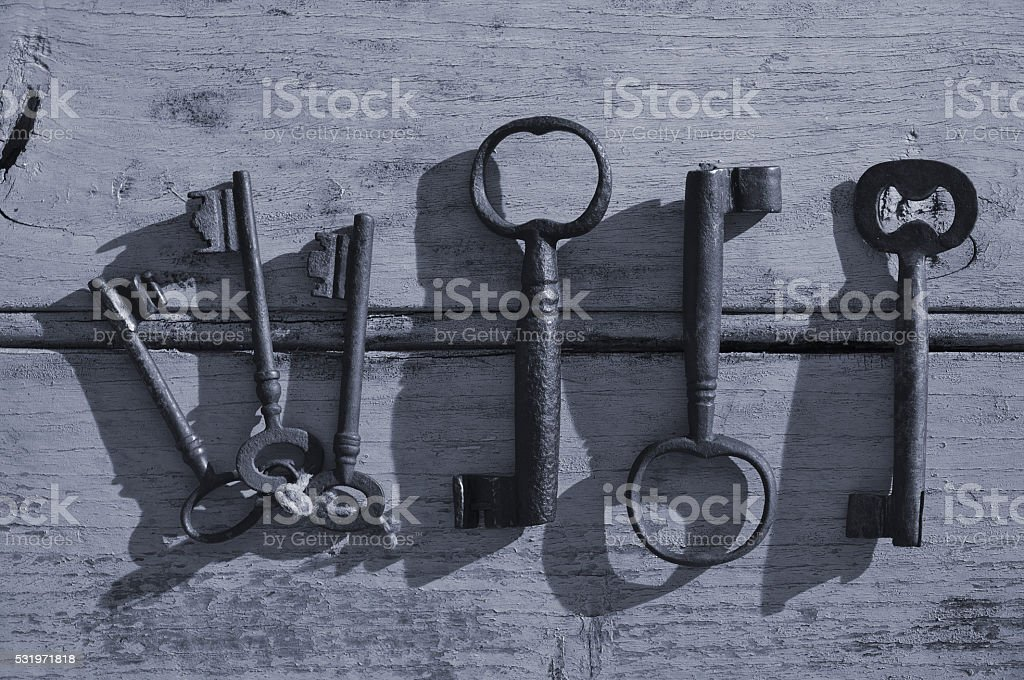 Skeleton keys on a wooden surface in Monochrome stock photo