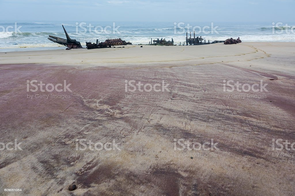 skeleton remains of old ship on coast, with reddish-pink sand stock photo