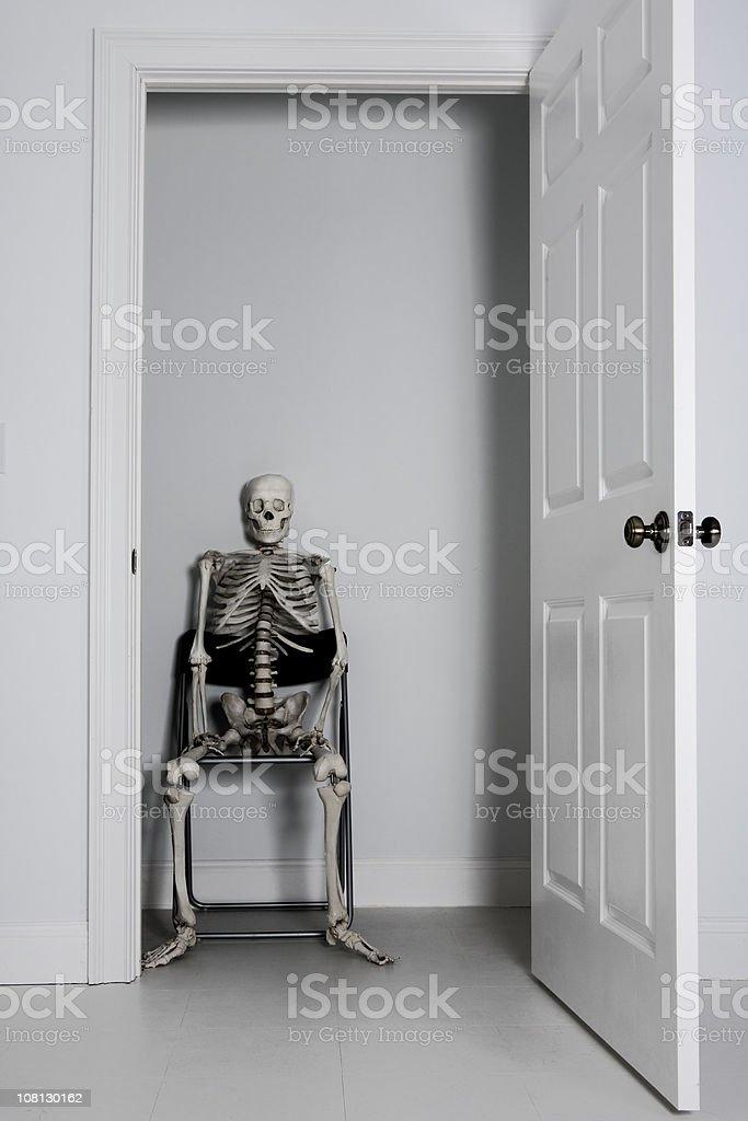 Skeleton Sitting in Empty Closet stock photo
