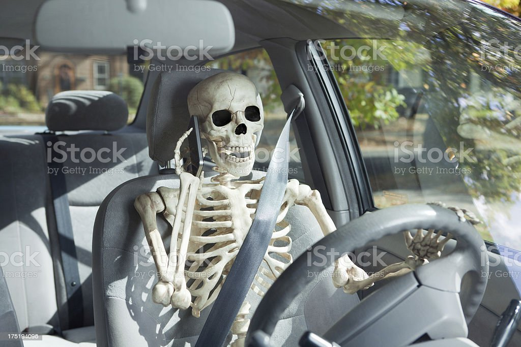 Skeleton Unsafely Driving Car, Talking on Mobile Phone, Inviting Accident stock photo