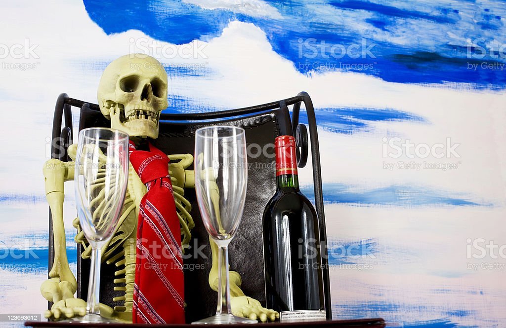 Skeleton waiting for his date bottle and two glasses. royalty-free stock photo