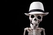 Skeleton wearing white hat