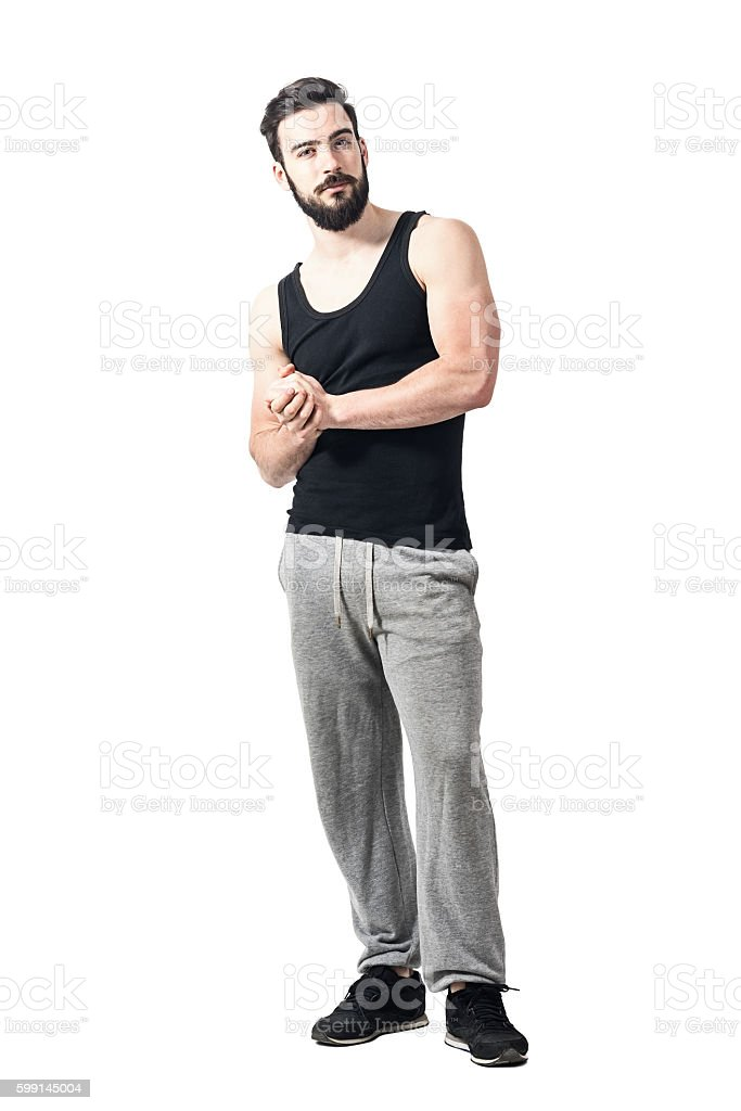 Skeptical athlete in sportswear with clasped hands looking at camera stock photo