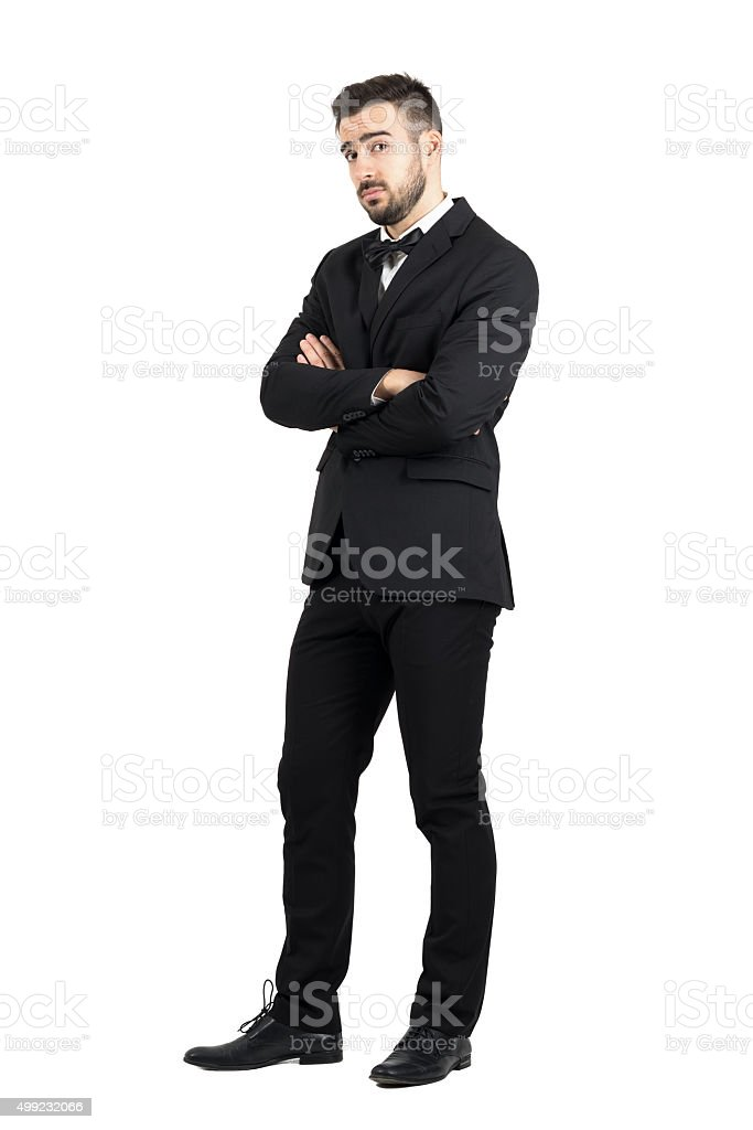 Skeptical defensive man with crossed arms looking at camera suspiciously stock photo