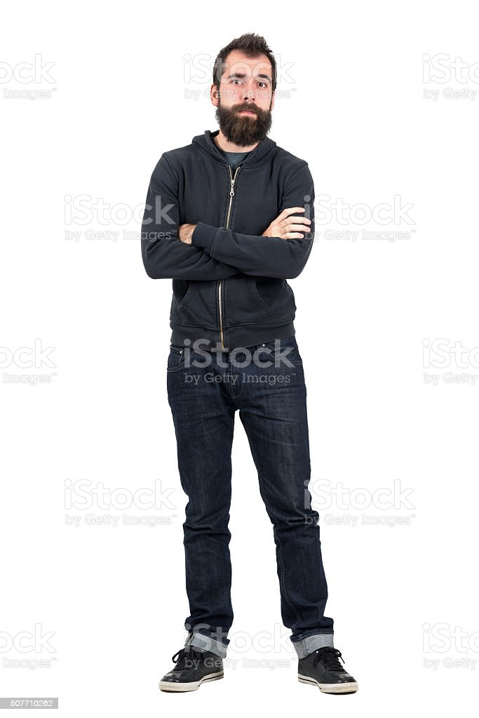 Skeptical hipster in black hooded sweatshirt with crossed arms stock photo