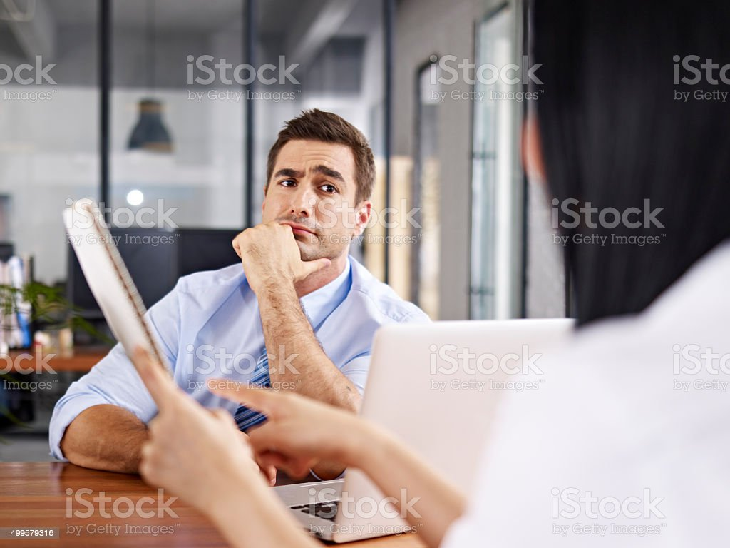 skeptical interviewer looking at interviewee stock photo