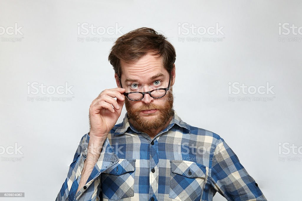 Skeptical man lowering his eyeglasses and looking with reproach stock photo