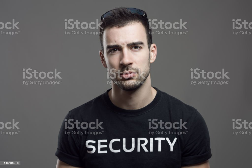 Skeptical security guard looking at camera with sunglasses on head stock photo