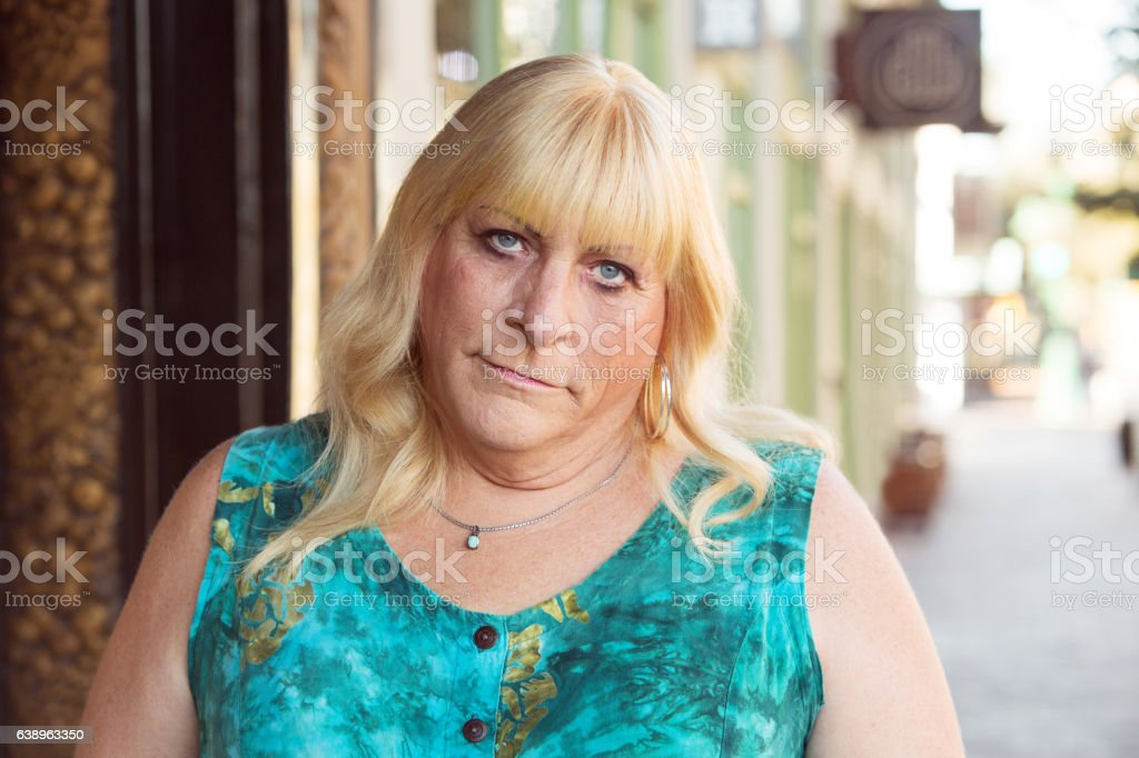 Skeptical transgender woman in green dress stock photo