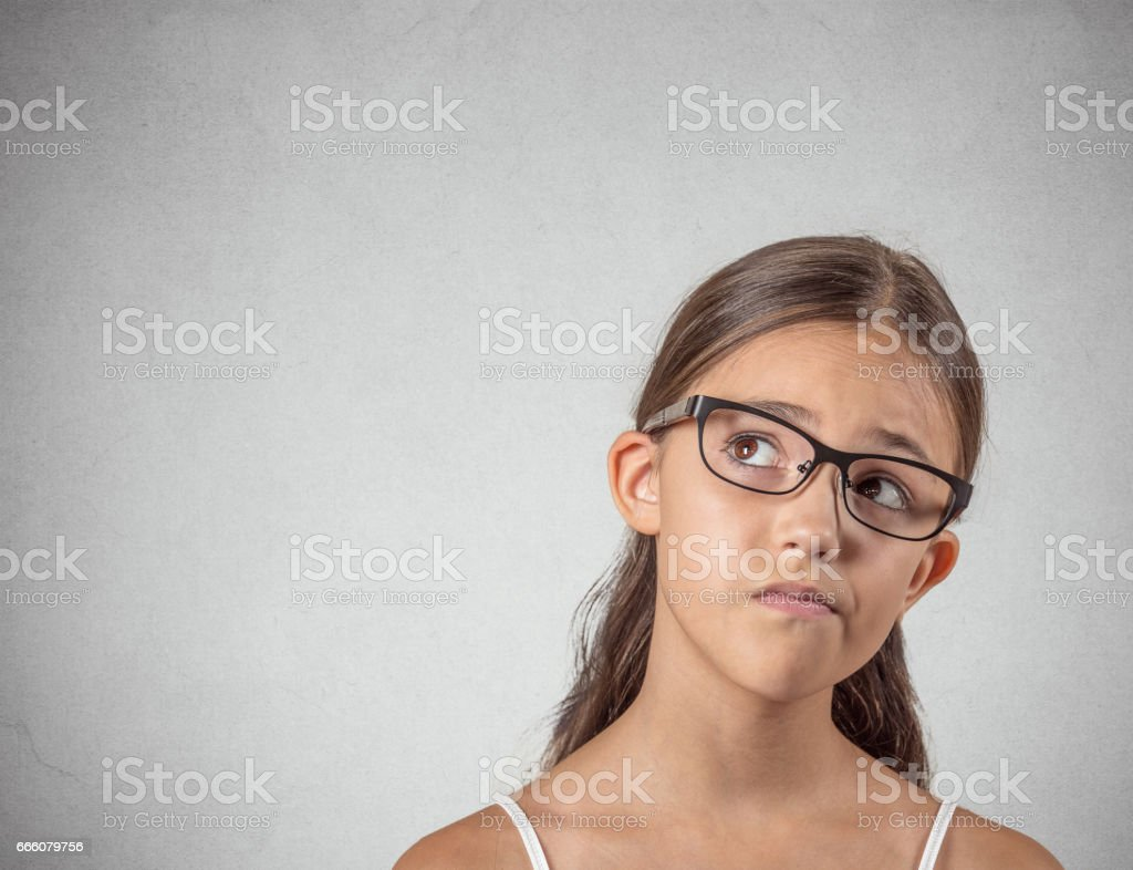 skeptical young girl looking up, suspicious, skepticism on face stock photo