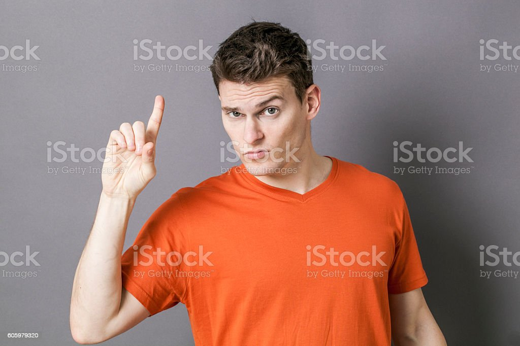 skeptical young sportsman raising index, watching out or expressing doubt stock photo