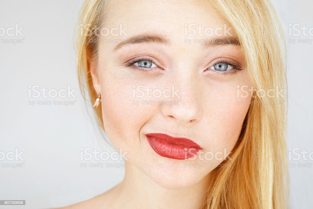 Skeptically smiling at camera red-haired woman stock photo