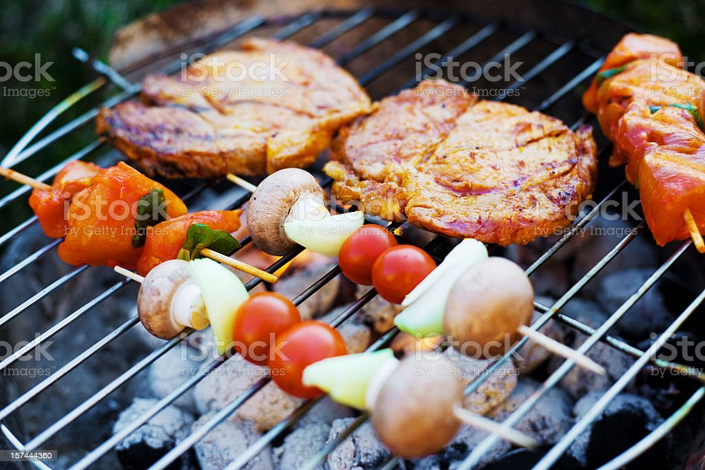 Skewer and meat on a grill stock photo