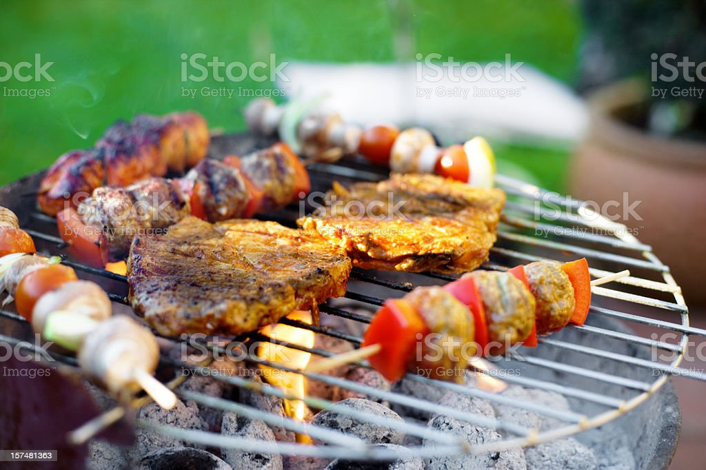 Skewer and meat on grill stock photo