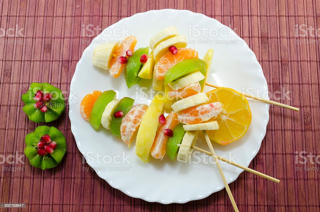 Skewered bananas, kiwis, oranges, lemons, pomegranate royalty-free stock photo