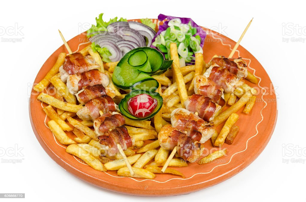 skewers decorated with salad and french fries stock photo