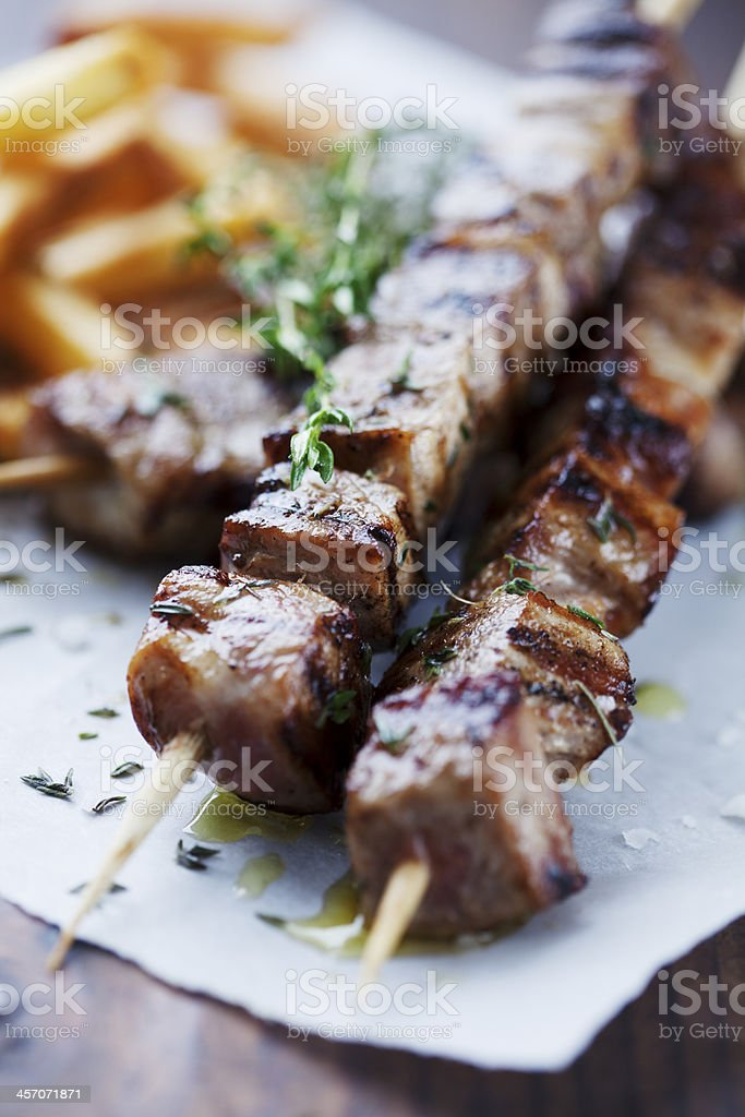 Skewers of roasted meat on a blue napkin stock photo
