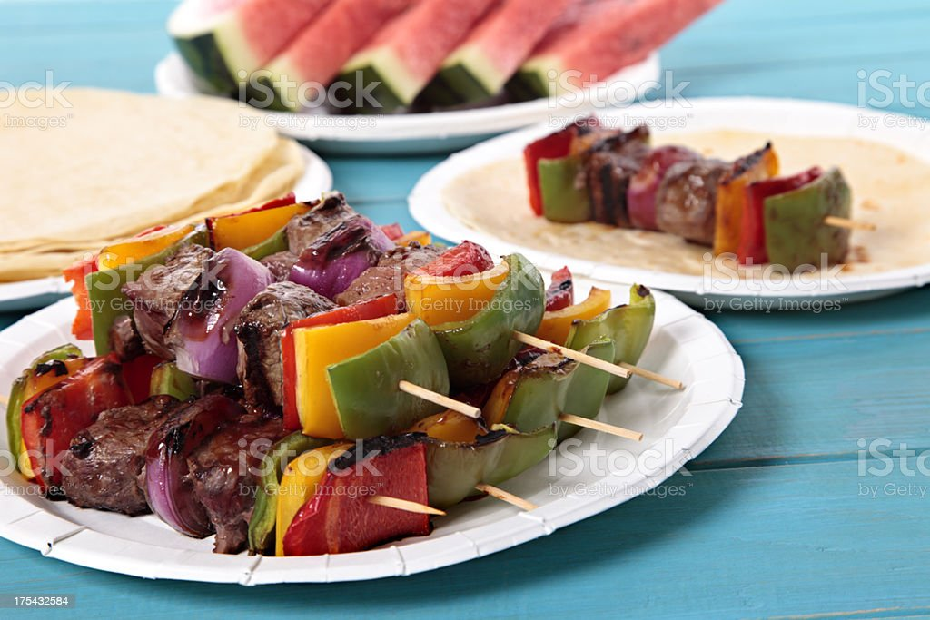 BBQ skewers, watermelon, and tortillas, atop a picnic table stock photo