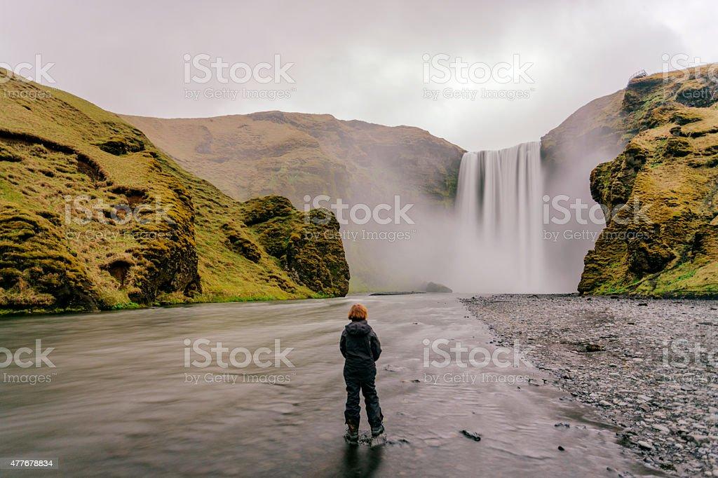 Skógafoss, a young girl stands at Skógafoss waterfall, motion blur stock photo