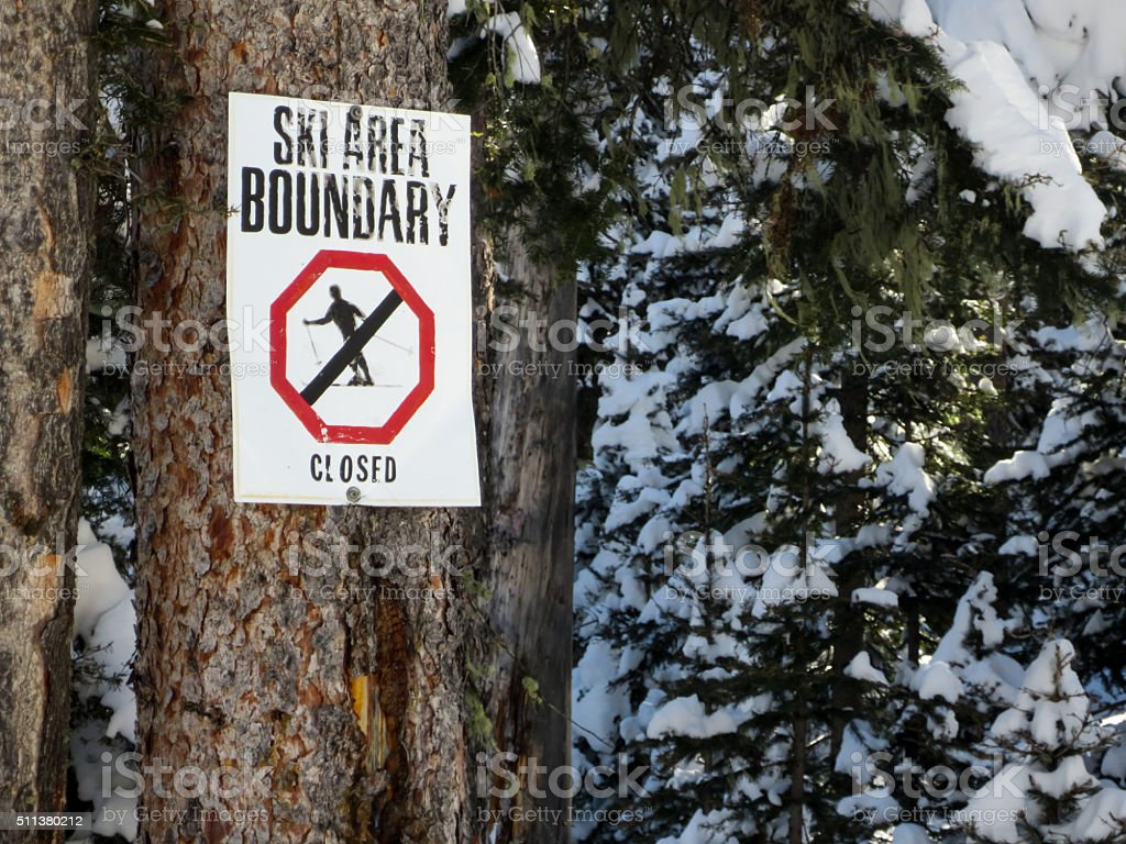 Ski area boundary sign on a pine tree stock photo
