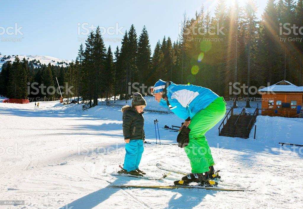 Ski instructor talking to a small boy on ski slopes. stock photo