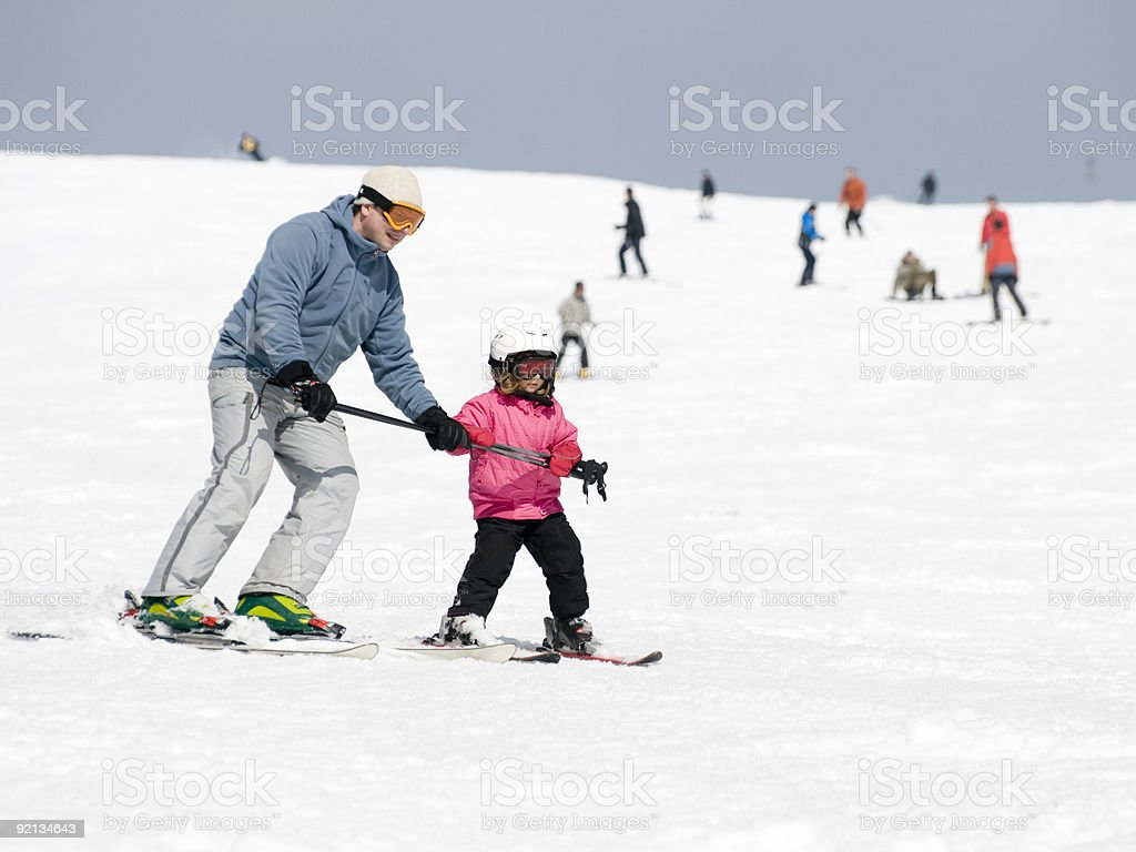 A ski instructor teaches a child how to make a proper turn  stock photo