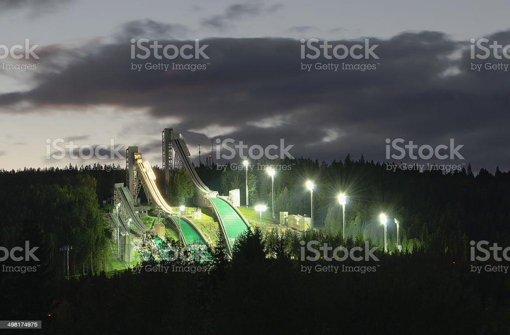 Ski jumping hills in night-time lighting stock photo