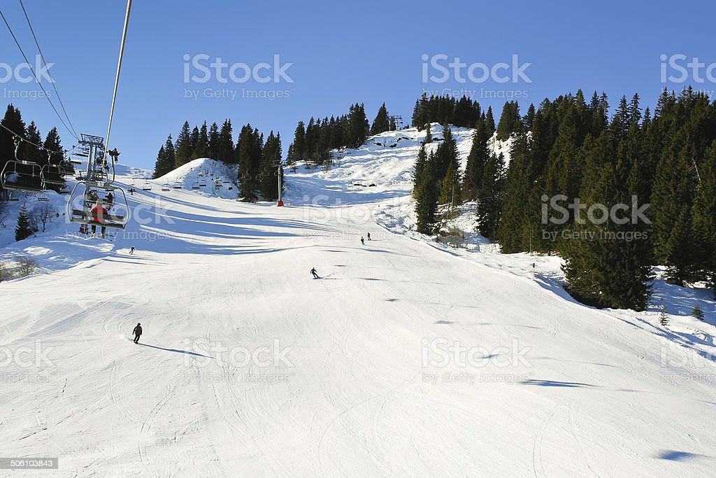 ski lift and skiing tracks on snow Alps mountains stock photo